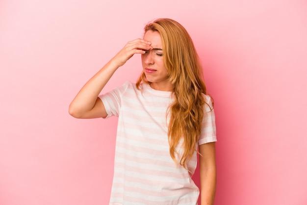 Femme blonde caucasienne isolée sur fond rose ayant un mal de tête, touchant le devant du visage.