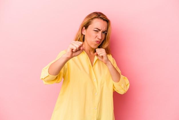 Femme blonde caucasienne isolée sur fond rose jetant un coup de poing, colère, combat à cause d'une dispute, boxe.