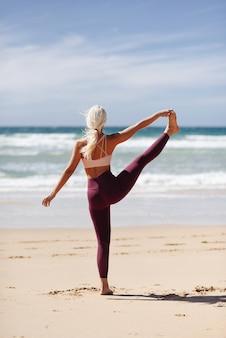 Femme blonde caucasienne, pratiquer le yoga sur la plage