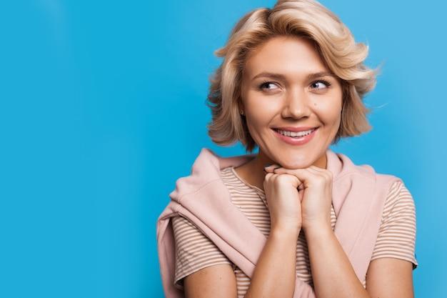 Femme blonde caucasienne rêveuse souriante et à la recherche de l'espace libre près d'elle sur un fond bleu