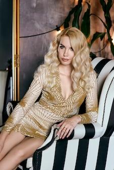 Femme blonde caucasienne en robe dorée dans un fauteuil à la fête