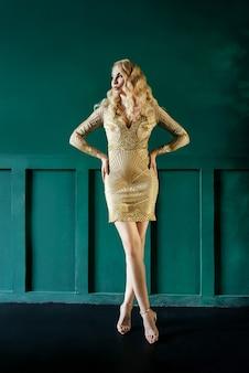 Femme blonde caucasienne en robe dorée à la fête