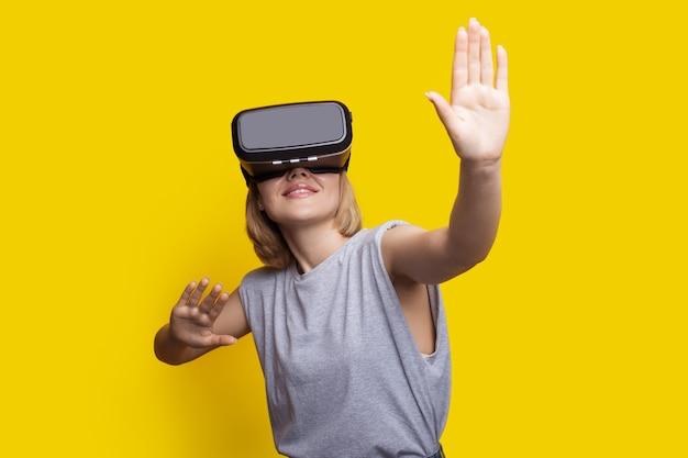 Femme blonde caucasienne touche quelque chose tout en faisant l'expérience d'un nouveau casque de réalité augmentée sur un mur de studio jaune