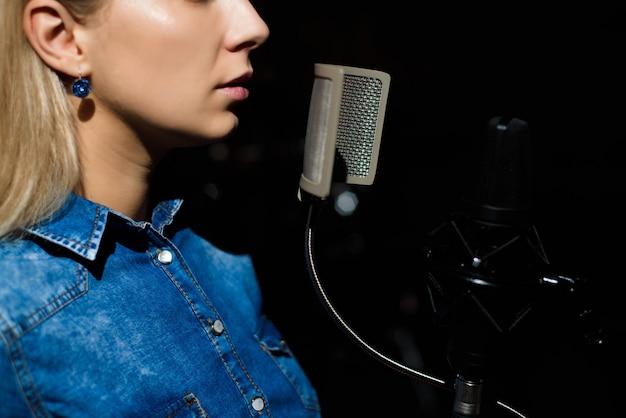 Femme blonde chante dans un studio d'enregistrement