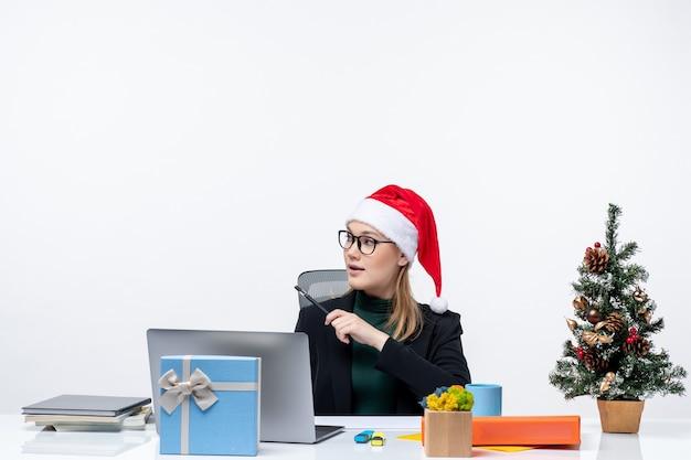 Femme blonde avec un chapeau de père noël assis à une table avec un arbre de noël et un cadeau