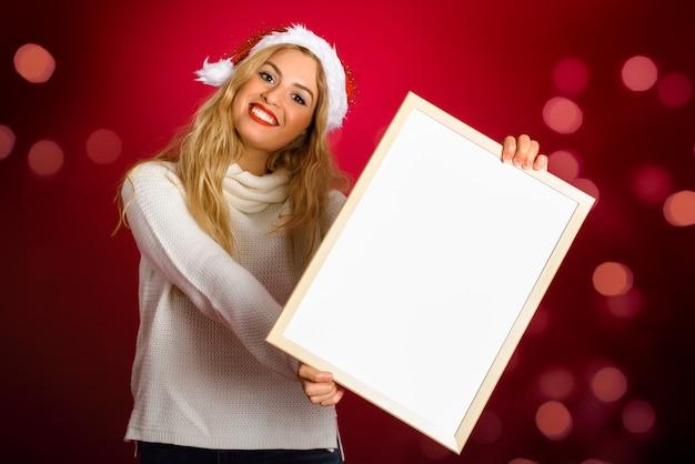 Femme blonde avec un chapeau de père noël tenant tableau blanc