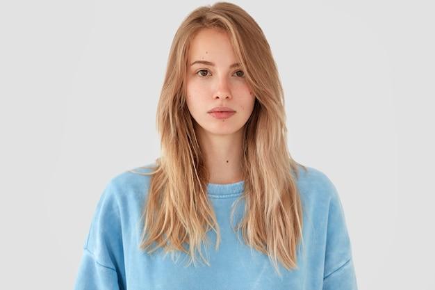 Femme blonde en chemise bleue posant