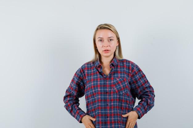 Femme blonde en chemise à carreaux main dans la main sur le ventre, posant à la caméra et à la charmante vue de face.