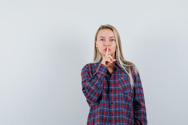 Femme blonde en chemise à carreaux mettant l'index sur la bouche et montrant le geste de silence et à la recherche attrayante, vue de face.