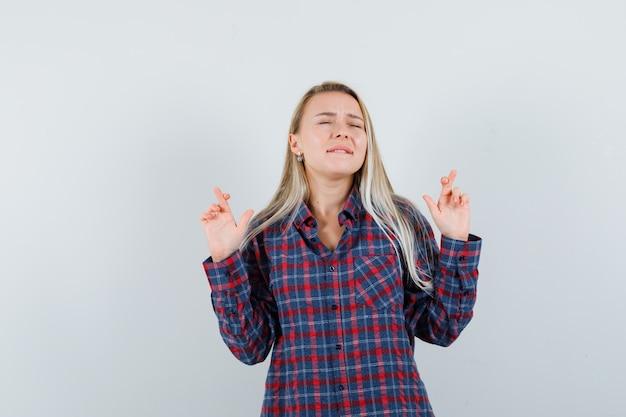 Femme blonde en chemise à carreaux tenant les doigts croisés, mordre les lèvres et à la vue de face, heureux.