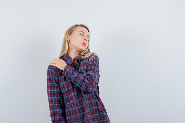Femme blonde en chemise à carreaux tenant la main sur l'épaule et à la vue épuisée, de face.