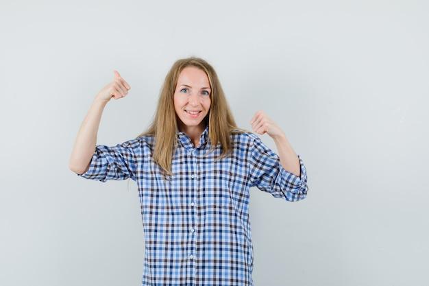 Femme blonde en chemise montrant deux pouces vers le haut et à la recherche de plaisir,