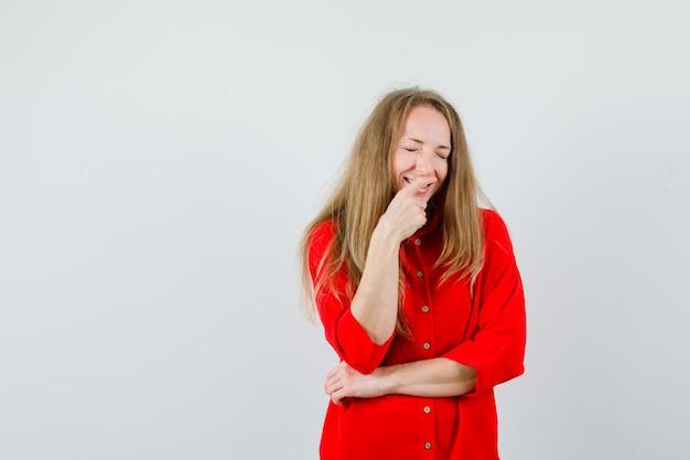 Femme blonde en chemise rouge tenant le doigt sur la bouche et l'air heureux,