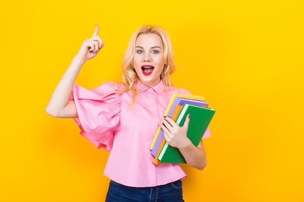 Femme blonde en chemisier rose avec une pile de livres