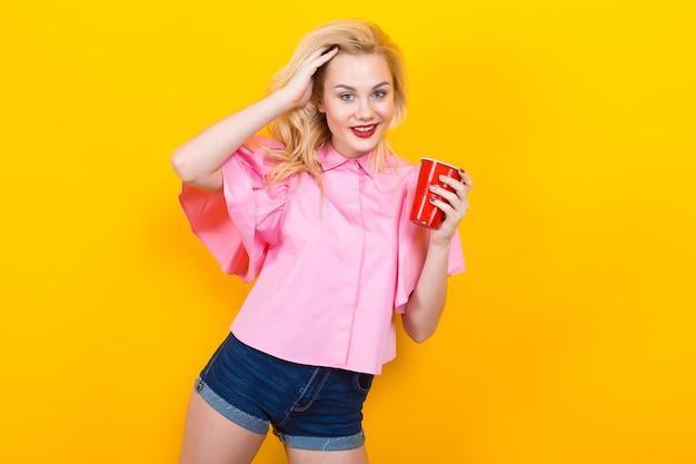 Femme blonde en chemisier rose avec une tasse rouge