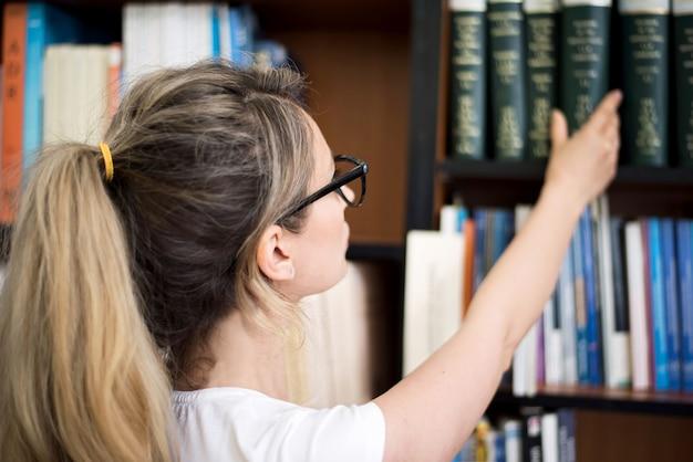Femme blonde en choisissant un livre de l'étagère