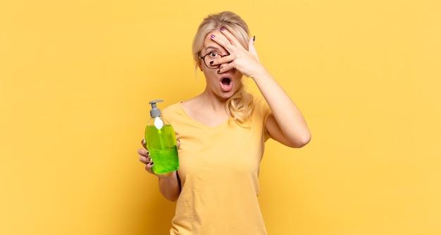 Femme blonde à la choqué, effrayé ou terrifié, couvrant le visage avec la main et furtivement entre les doigts