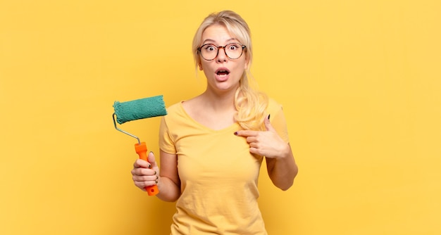 Femme blonde à la choqué et surpris avec la bouche grande ouverte, pointant vers soi