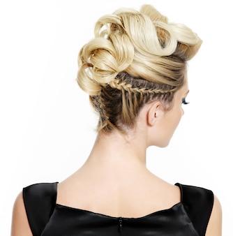 Femme blonde avec une coiffure créative bouclée sur blanc
