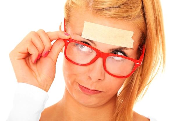 Une femme blonde confuse avec une bande sur son front et un espace pour votre texte