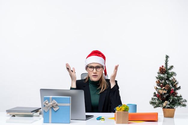 Femme blonde confuse avec un chapeau de père noël assis à une table avec un arbre de noël et un cadeau sur elle et interroger quelque chose dans le bureau sur fond blanc