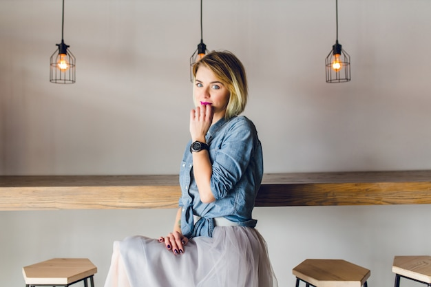 Femme blonde coquette aux yeux bleus et lèvres rose vif assis dans un café sur une chaise, boire du café