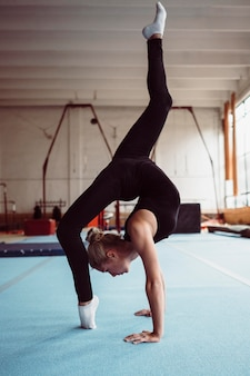 Femme blonde sur le côté de la formation pour le championnat de gymnastique