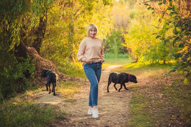 Une femme blonde avec une coupe courte se promène dans la forêt dans un pull en tricot et deux gros chiens noirs rottweiler. randonnée en plein air dans la forêt d'automne