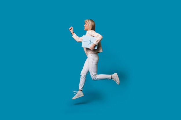 Femme blonde en cours d'exécution tient une boîte cadeau sur un mur de studio bleu et sourire dans des vêtements décontractés