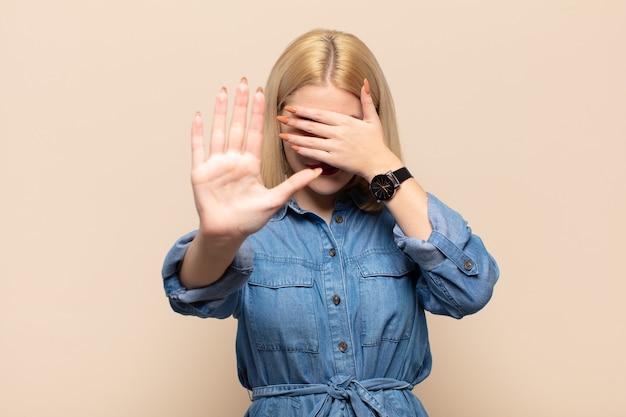 Femme blonde couvrant le visage avec la main et mettant l'autre main à l'avant pour arrêter la caméra, refusant des photos ou des images
