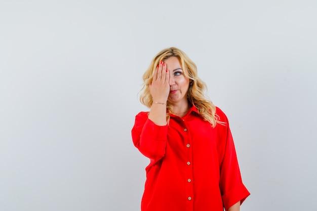 Femme blonde couvrant les yeux avec une main en chemisier rouge et à la recherche de bonheur.