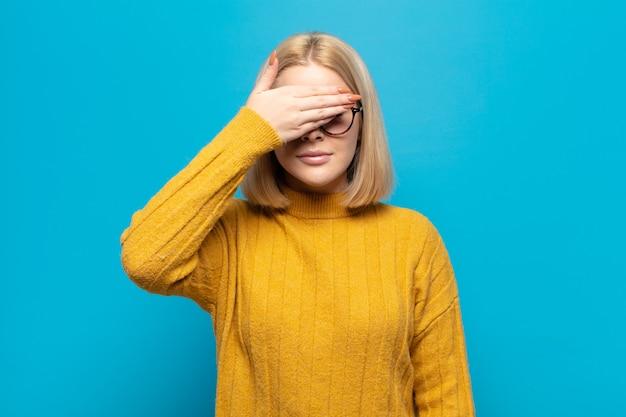 Femme blonde couvrant les yeux d'une main se sentant effrayée ou anxieuse, se demandant ou attendant aveuglément une surprise
