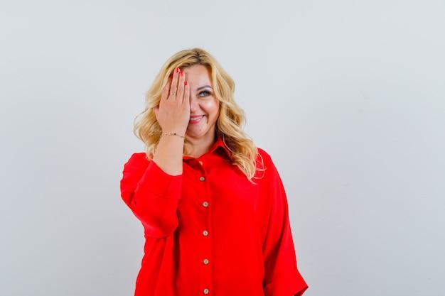 Femme blonde couvrant les yeux avec les mains en chemisier rouge et à heureux,