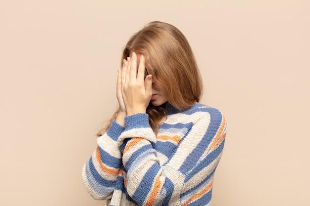Femme blonde couvrant les yeux avec les mains avec un regard triste et frustré de désespoir, de pleurs, de vue latérale