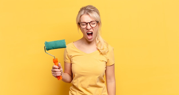 Femme blonde criant de manière agressive, à la très en colère, frustré, indigné ou agacé, crier non