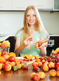 Femme blonde cuisine salade de fruits
