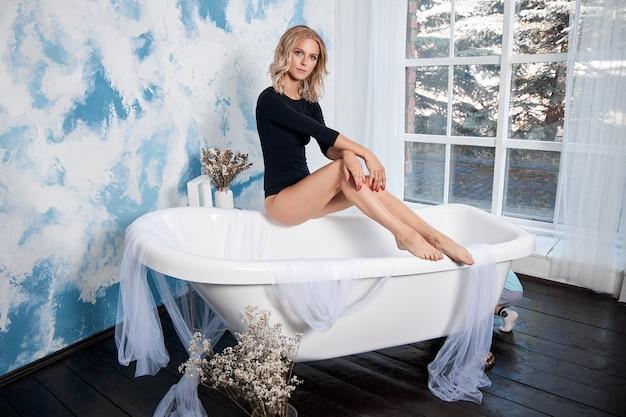 Femme blonde dans un body noir dans la salle de bain. portrait de beauté d'une fille, nettoyer la peau délicate du visage et du corps