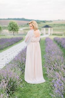Femme blonde dans un champ de lavande portant une robe longue élégante et légère le jour d'été nuageux
