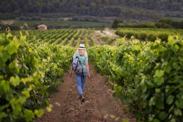 Femme blonde dans un chapeau marche parmi les raisins sur le vignoble de provence france