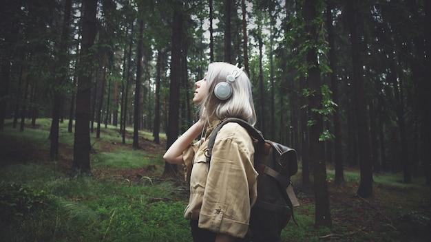Femme blonde, dans, écouteurs, à, sac à dos, dans, jour pluvieux, dans, forêt