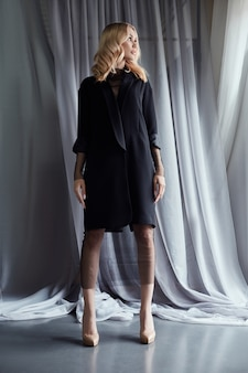 Femme blonde dans un manteau d'automne noir