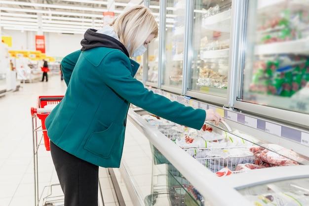 Une femme blonde dans un masque médical choisit des produits dans le service de congélation d'un supermarché. précautions lors de la pandémie de coronavirus.