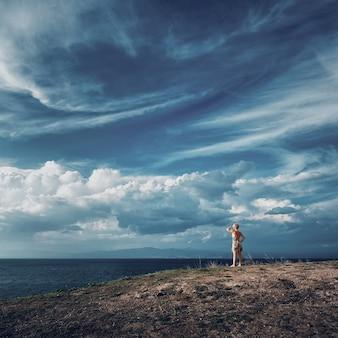 Femme blonde debout au sommet de la colline et surplombant la mer beau ciel sur la mer égée
