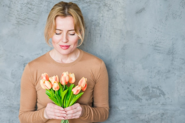 Femme blonde debout avec bouquet de tulipes