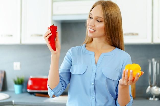 Femme blonde debout dans la cuisine et la cuisine