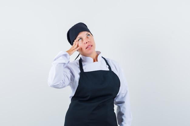 Femme blonde debout dans la pensée pose, penchée joue sur la main en uniforme de cuisinier noir et à la pensif.