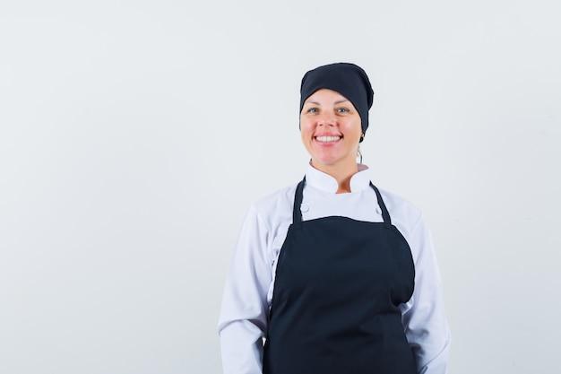 Femme blonde debout droite et posant à l'avant en uniforme de cuisinier noir et à la jolie.