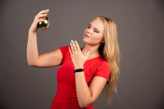 Femme blonde debout sur un mur noir avec horloge.