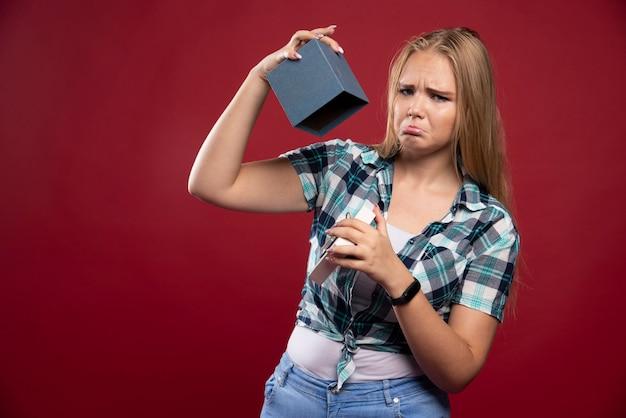 Une femme blonde devient triste et confuse en ouvrant une boîte-cadeau.