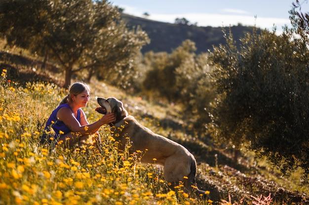 Femme blonde avec un dogue espagnol sur un champ de fleurs jaunes